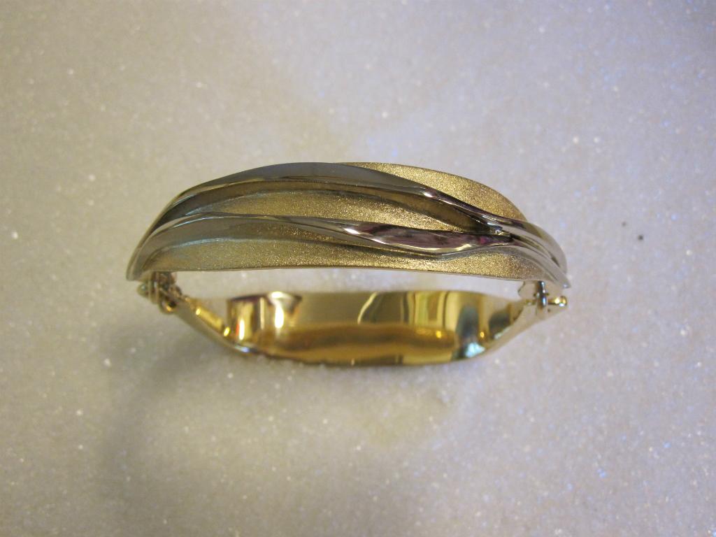 Armbånd smidd i gult og hvitt gull.