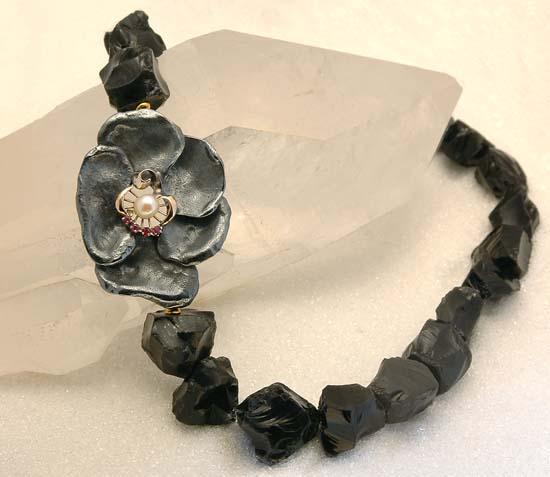 Lås / anheng i oksidert sølv og gult gull med rubiner og perle. Halskjede i obsidian.