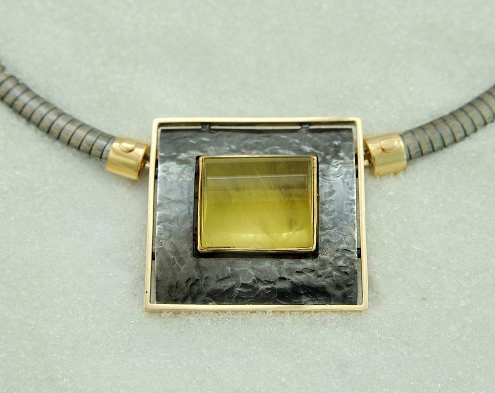 Brosje / lås i oksydert sølv og gull med en gylden beryllcabochon. Halskjede i oksydert sølv og gull.