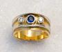 Ring i gult gull med diamanter og safir.