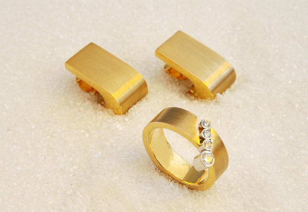 Ring og tilhørende ørepynt i gult gull med diamanter.