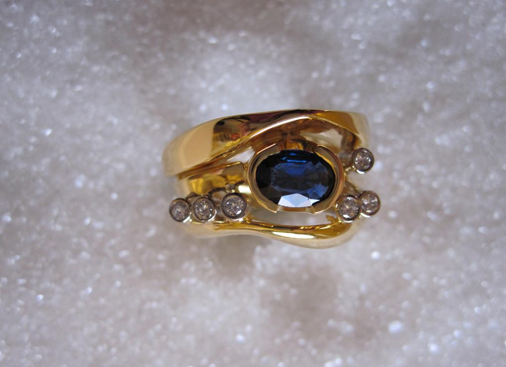 Ring smidd i gult og hvitt gull med safir og diamanter.