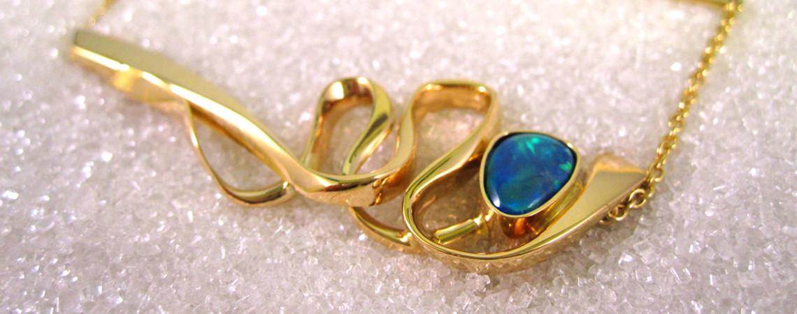 Slipsnål smidd i gult gull med opal