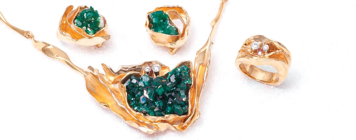 Nordlys, smykkesett i gult gull med anheng/lås med dioptaskrystall, diamanter og kjede Billow, øresmykker med dioptaskrystall samt ring med to diamanter.